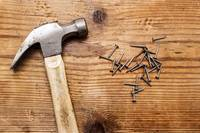 Hammer & pile of rivets, nails on wood background