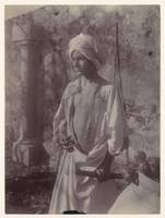 [Young Man in White Robe and Head Gear Holding Sca