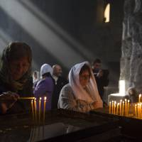 Women praying at Tatev Monastery in Armenia Art Prints & Posters by Joel Carillet