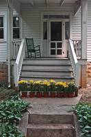 flower pots at foot of porch stairs