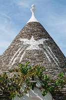 Symbol in Trullo conical rooftop in Alberobello