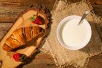 Breakfast with croissant, strawberries and milk