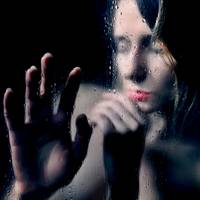 Woman portrait behind glass with rain drops