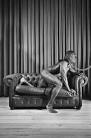 Beautiful naked man with mask posing on a sofa