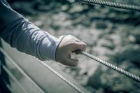 Young boy hand holding metal wire fence