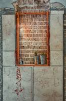 Window sealed with red bricks in an abandoned buil
