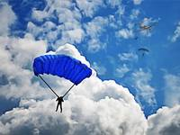 Group of Skydivers Among Puffy White Clouds
