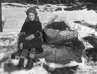 Girl sitting by a rune stone fragment in Lissma, H