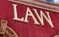 Law Sign on Crimson Red Stucco Wall