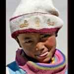 """Child in Tibet with Buddhist deer hat"" by ExposedPlanet"