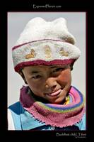 Child in Tibet with Buddhist deer hat