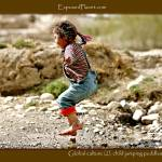 """Global culture: little girl jumping puddles in Tib"" by ExposedPlanet"