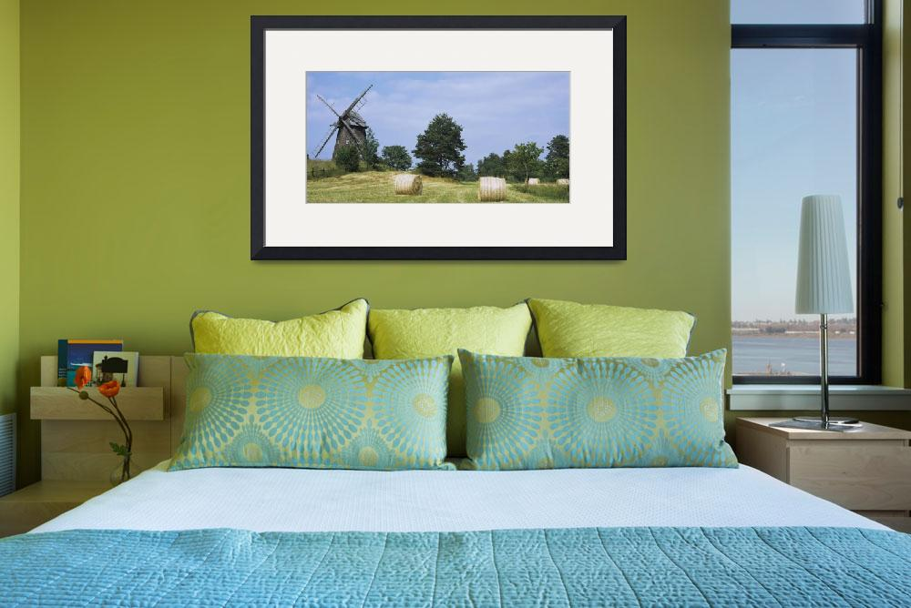 """Hay bale in a field with a traditional windmill i&quot  by Panoramic_Images"