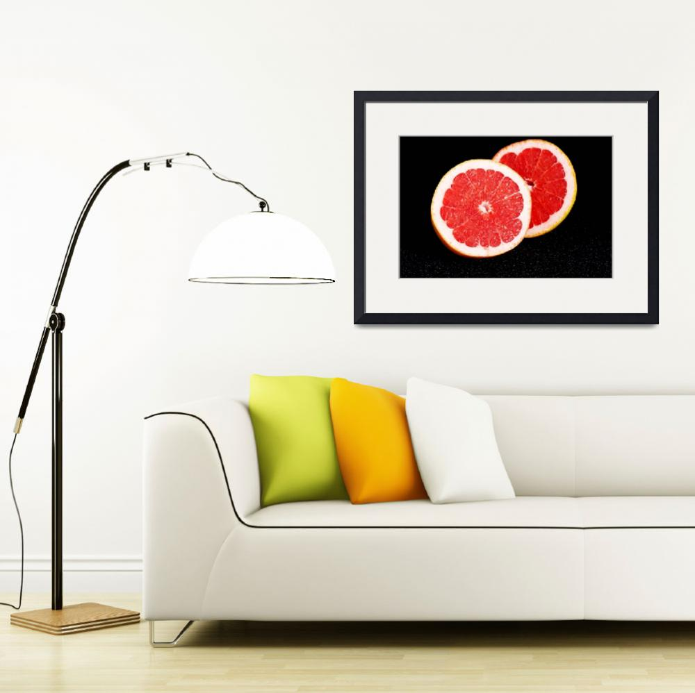 """Fresh grapefruit divided into two pieces. On black&quot  by Piotr_Marcinski"