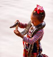 Portrait Little Girl with Snake, Cambodia in Reds