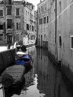 Blue boat on a black and white canal