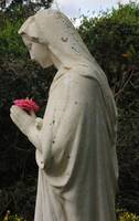 left facing woodland statue adoring pink blossom