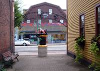 Frog Sculpture looks accross Main St. at Sara's St by Sara Fraser