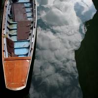 reflected clouds and a boat Art Prints & Posters by Jon Rawlinson