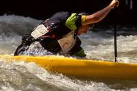 Whitewater kayaker charges the gate