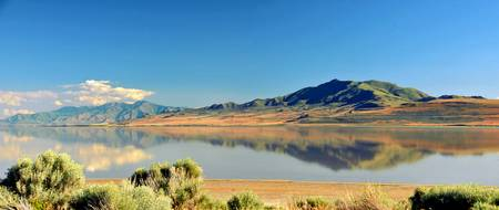 antelope island reflected in water near causeway