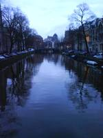 Bare trees reflected on an Amsterdam canal