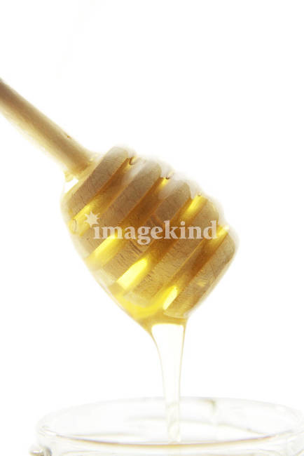 Wooden honey drizzler with a honey