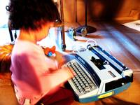 child typing on typewriter