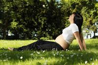 Beautiful pregnant woman relaxing in the park.