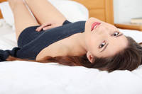 Young and beautiful brunette woman on bed.