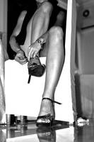 woman with long legs fixing shoe on chair