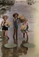 Amana girls standing in water holding bunches