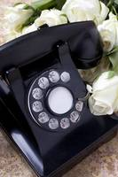 Old phone and white roses