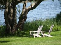 White Adirondack Chairs By The River's Edge