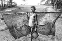 Boy with a fishing net and a bucket in his hands g