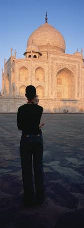 Rear view of a tourist taking a photograph of a m