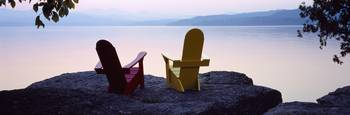 Red and Yellow Adirondack chairs on a rock near a