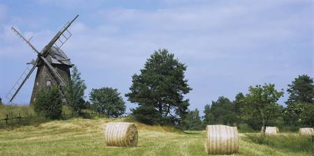 Hay bale in a field with a traditional windmill i