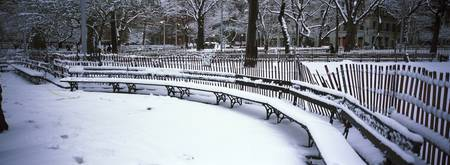 Snowcapped benches in a park