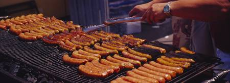 Close-up of a mans hand cooking hot dogs on a bar