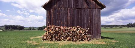 Pile of firewood in front of a barn