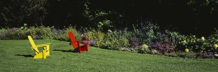 Red And Yellow Adirondack Chairs On A Lawn