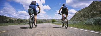 Rear view of two people cycling on a road