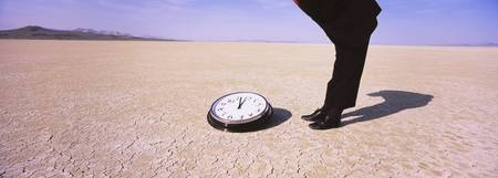 Businessman looking at a clock in a desert