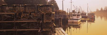 Stack of lobster trap with motorboats moored at a