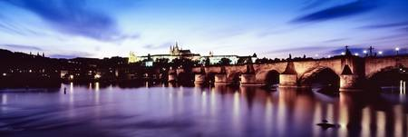 Arch bridge across a river with a cathedral in th