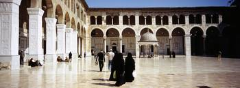 Group of people walking in the courtyard of a mos