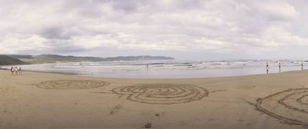Circular patterns drawn in sand on the beach Knys