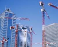 Low angle view of cranes in front of buildings