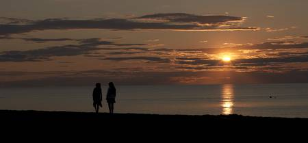 Silhouette of two people on the beach at sunset